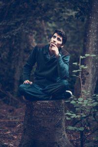 Man sitting on tree stump thinking.